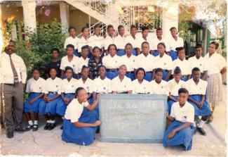 Photo de classe de jeunes filles portant une chemise blanche à manches courtes et une jupe bleue.