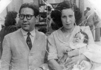 Un homme et une femme avec un bébé dans ses bras.