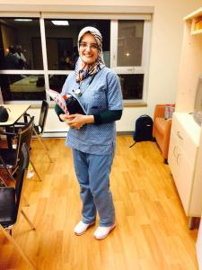 Photo plein pied d'une infirmière avec un stéthoscope autour du cou et tenant un cartable et différents objets.