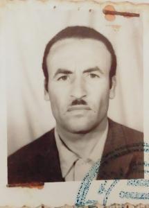 Photo noir et blanc prise dans une cabine photographique d'un homme portant une moustache.