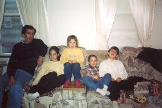 Une famille assise sur un divan.