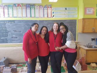 Quatre femmes qui se tiennent bras dessus, bras dessous.