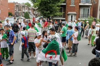 Une foule arborant le drapeau de l'Algérie. En arrière-plan, des maisons