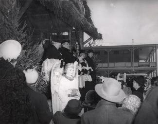Aux côtés de quatre ecclésiastiques, monseigneur Paul-Émile Léger donne sa bénédiction sur les ondes de CKAC de la crèche extérieure de l'Oratoire le 25 décembre 1950. Près de la scène, plusieurs personnes et un petit ange mécanique.
