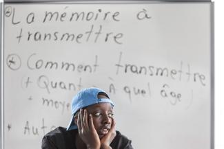 """Un garçon portant une casquette se tient la tête entre les mains. Derrière lui, un tableau sur lequel on peut lire """"La mémoire à transmettre"""""""
