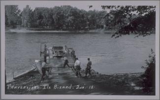Carte postale en noir et blanc montrant un traversier accosté avec une voiture à son bord et trois cyclistes qui se préparent à embarquer. On voit un quatrième homme devant le traversier.