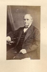 Photo en noir et blanc d'un homme d'âge mûr de la bourgeoisie, assis, portant un complet.