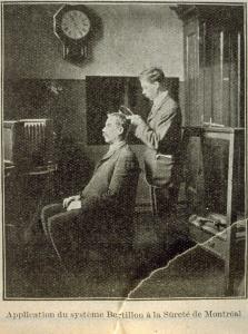 Coupure de journal en sépia qui montre une scène d'intérieur. Un homme debout mesure la tête d'un second homme assis sur une chaise, vue de profil.
