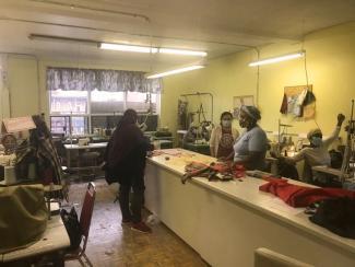 Cinq personnes sont dans un atelier de couture, deux assises devant des machines à coudre et trois debout autour d'une table haute.
