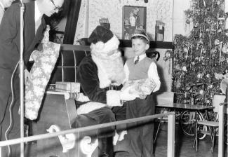 Photo en noir et blanc d'un enfant avec le père Noël qui lui remet un cadeau.