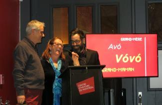 Deux hommes et une femme sont debout derrière un lutrin et un micro. Un écran montre les mots Avó, Vóvó, Grand-mère et Grand-maman sur un fond rouge.