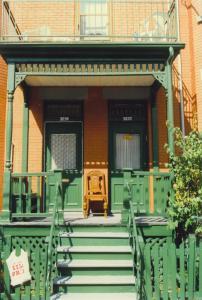 Photographie couleur de la façade d'un duplex avec un balcon peint en vert et deux portes au-dessus de chacune desquelles se trouve une plaque d'adresse bleu et blanc.