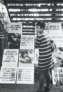 Une jeune femme debout, devant des slogans et photographies à caractère révolutionnaire installée au dos d'un escalier.