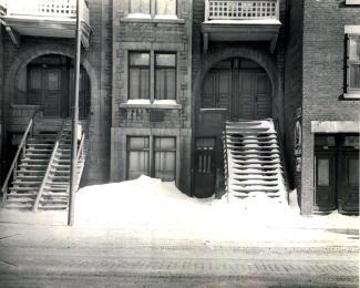 Photographie d'un bâtiment anonyme en pierre et en brique dont les entrées sont sous des arches. Il y a des escaliers qui partent du perron et donnent sur la rue.