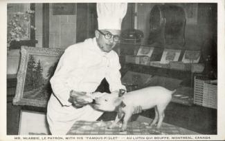 Le propriétaire Joseph McAbbie nourrissant un porcelet dans son restaurant.