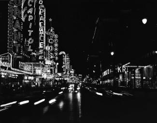 Photo en noir et blanc montrant la rue Sainte-Catherine de nuit avec les enseignes néon.
