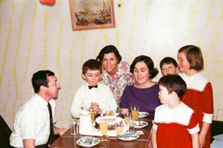 Trois adultes et quatre enfants sont autour d'une table où se trouve un gâteau d'anniversaire et des jus.