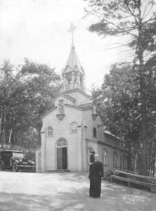 Frère André devant la petite chapelle d'origine en 1921.