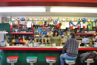 Photo couleur de l'intérieur d'un commerce avec comptoir lunch. Un homme est assis sur un tabouret, de dos, et une femme est debout derrière le comptoir.