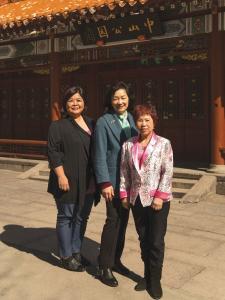 Photo couleur plein pied de trois femmes souriantes posant debout sur la place Sun-Yat-Sen dans le Quartier chinois.