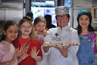 Une chef tenant un plateau de nourriture est entourée de quatre petites filles souriantes.