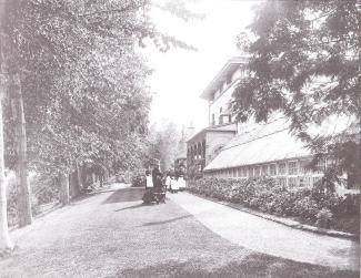 Photographie de Sergeant, son épouse et leurs aides domestiques de face dans un jardin bordant une demeure.
