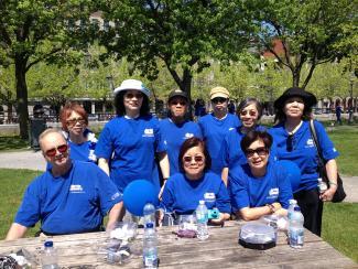 Neuf personnes portant un t-shirt bleu de la marche pour la Société Alzheimer prennent la pose et la pause dans un parc derrière une table de pique-nique.