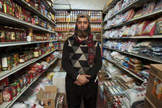Un homme debout dans son épicerie pakistanaise