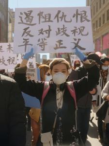 Une foule marche dans une rue du centre-ville. Plusieurs personnes tiennent des pancartes ou des bannières en chinois ou en anglais.