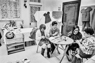 Quatre femmes sont assises et tricotent. Une table se trouve entre elles. On voit plusieurs de leurs réalisations dans la pièce derrière elles.