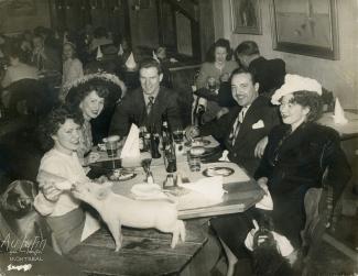 Trois femmes et deux hommes sont attablés dans un restaurant. La femme de gauche donne le biberon à un porcelet à l'avant-plan. À l'arrière-plan, on voit d'autres clients attablés.