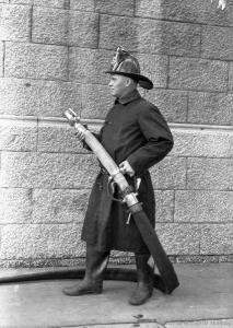 Photographie en pied d'un pompier en uniforme tenant un boyau et une lance d'incendie.