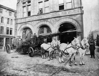 Pompiers et chevaux devant la caserne, affichant «CASERNE CENTRALE DE POMPIERS - CENTRAL FIRE STATION»