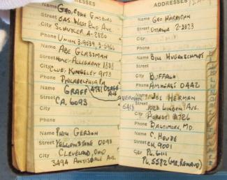 Petit carnet avec de l'écriture manuscrite à l'intérieur. Les onglets de droite sont très usés.