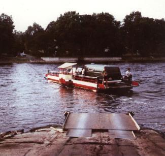 Photo couleur montrant un traversier avec deux véhicules à son bord sur une rivière. On aperçoit les deux rives.