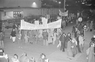 Des dizaines de personnes marchent dans la rue. Des manifestants tiennent une affiche pour le regroupement des garderies sans but lucratif.