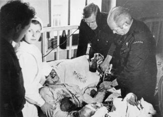 Photo en noir et blanc de deux médecins faisant une transfusion sanguine à un blessé, et une infirmière et un homme sont de l'autre côté du lit.