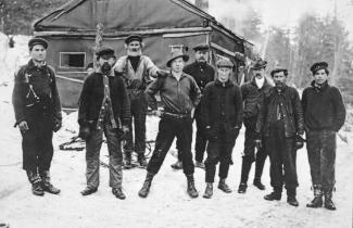 Photo noir et blanc de neuf hommes dans un camp de bûcherons en hiver