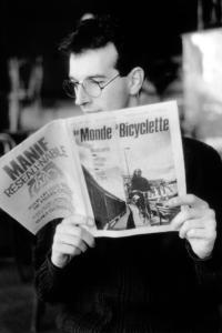 Homme lisant le bulletin Le Monde à bicyclette