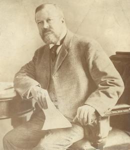 Photo d'un homme d'affaires assis, un coude sur une table et à la main un document.