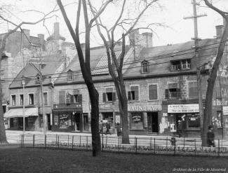 Photographie d'une enfilade de bâtiments en pierre abritant des commerces, dont «Laundry» et «A. Martin Bijoutier & Opticien».