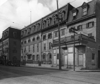 Photographie de la façade de l'hôpital Notre-Dame lorsqu'il était situé sur la rue Notre-Dame. On y remarque des poteaux électriques, les câbles servant à la circulation du tramway et deux voitures arrêtées devant l'hôpital.