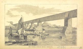 Vue générale du pont Victoria depuis les rives de Montréal. On aperçoit le pont à une voie ferrée, tel que construit initialement, sous forme d'un long tube reposant sur les piles de maçonnerie. Il y a quelques embarcations de petite taille en avant-plan.