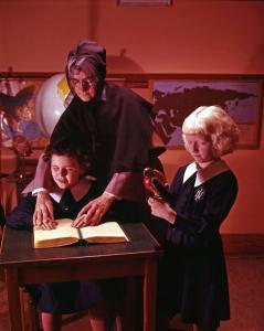 Une femme en costume de religieuse et une jeune fille posent leurs mains sur un livre. Une autre jeune fille se tient debout à leurs côtés.