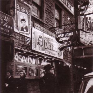 Photo en noir et blanc montrant la façade du Casa Loma. La chanteuse Carmen Déziel et le comédien fantaisiste Gabriel Bigras sont en vedette sur la marquise extérieure en mars 1957. Trois personnes circulent sur le trottoir devant l'édifice.