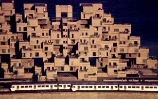 Vue d'ensemble du complexe Habitat 67 avec le train Expo Express devant.