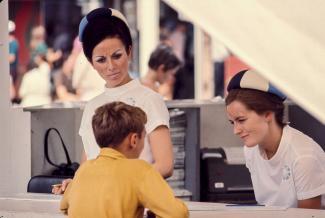 Un jeune garçon pose une question à deux hôtesses d'un kiosque d'information