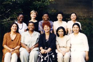 Cinq femmes assises et cinq femmes debout derrière. En arrière-plan, des arbres.