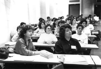 Photo noir et blanc d'un groupe de femmes assises et attentives dans une salle de conférence.