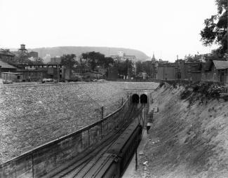 Photographie de la sortie du tunnel avec des bâtiments autour.et le mont Royal en arrière-plan.